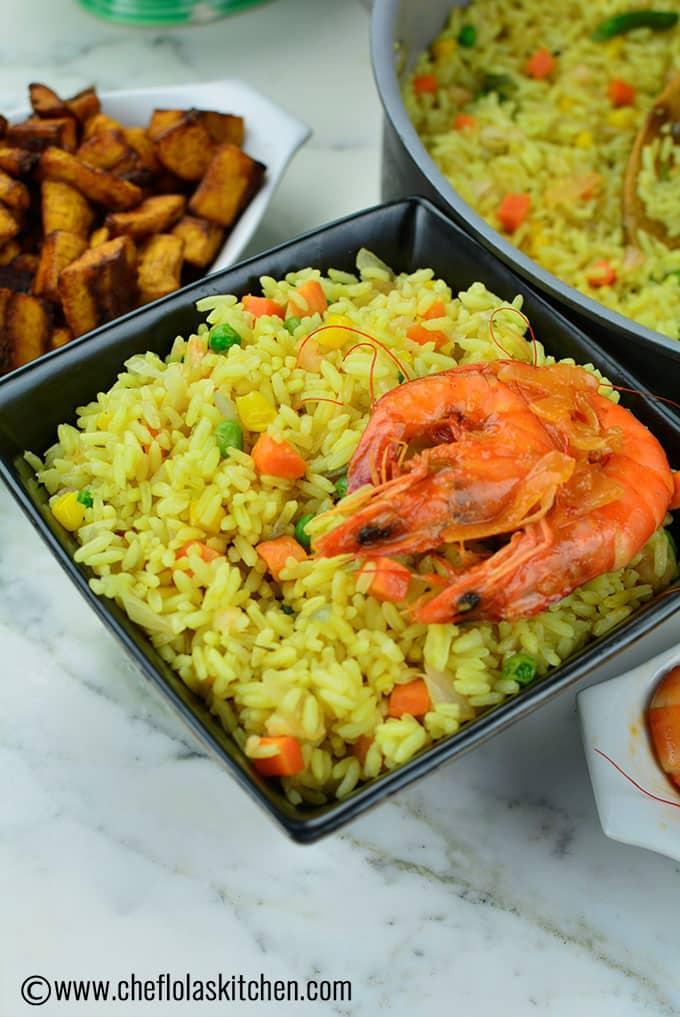 Close up view of Shrimp Fried Rice in a bowl with nigerian dodo serving beside it.