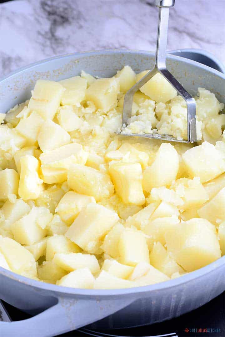 Easy Creamy Mashed Potatoes - Creamy mashed potatoes getting mashed with pepper and butter.