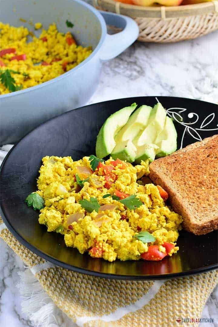scrambled tofu served in a plate with sliced bread