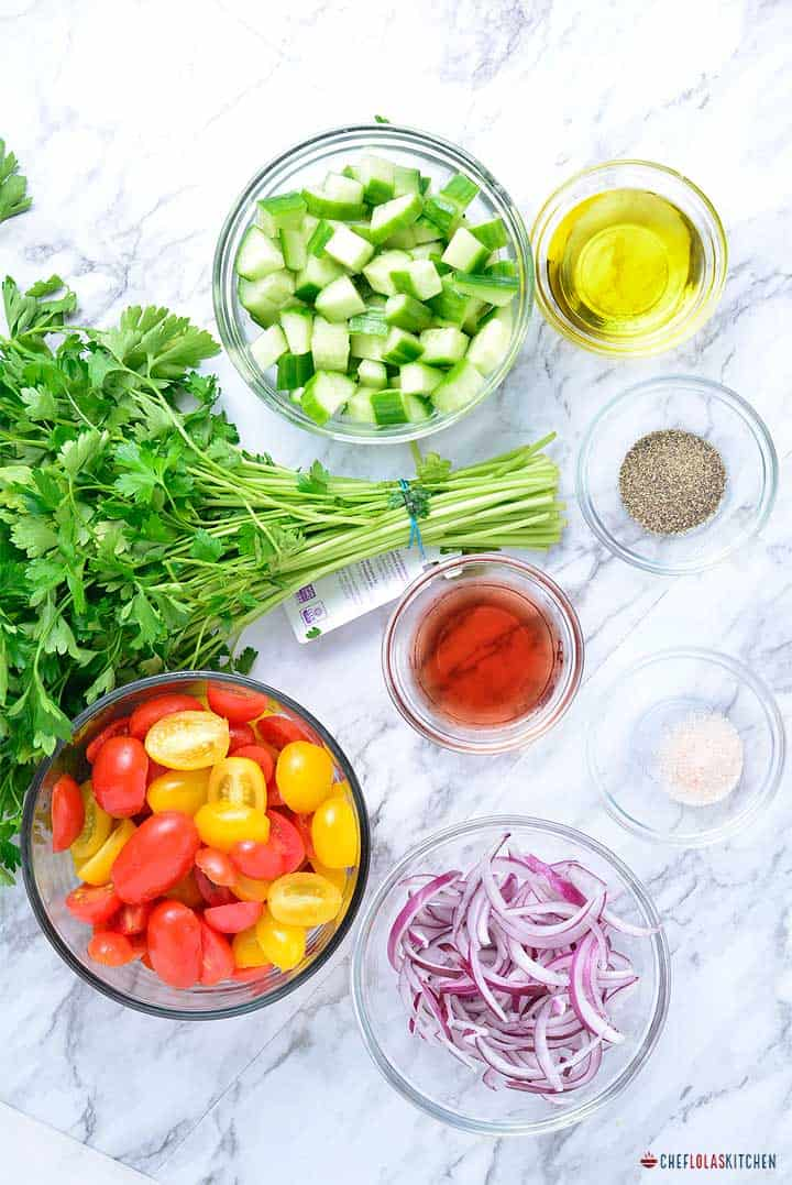 Ingredients for making cucumber Tomato Salad - tomatoes, cucumber, onions, olive oil, parsley, olive oil, salt and black pepper