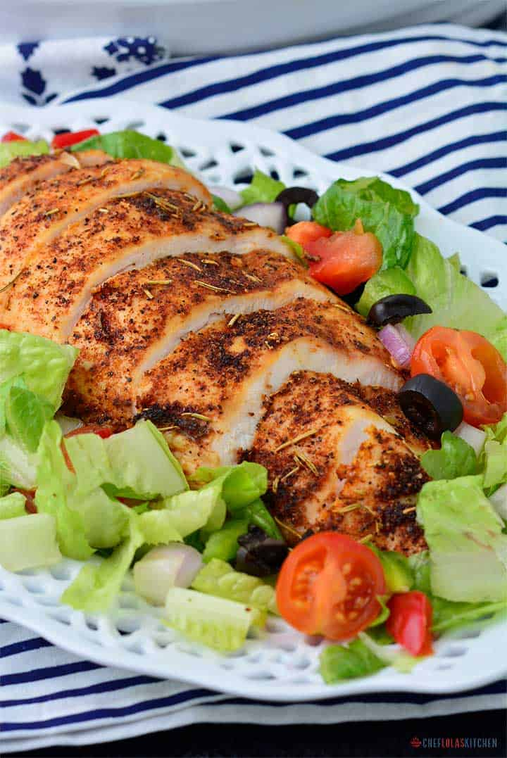Sliced Chicken Breasts served over a plate of salad