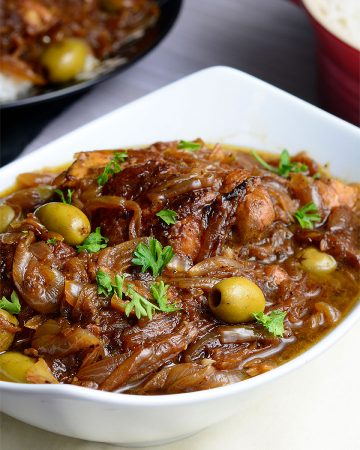Yassa Poulet served in a white bowl and garnished with parsley.