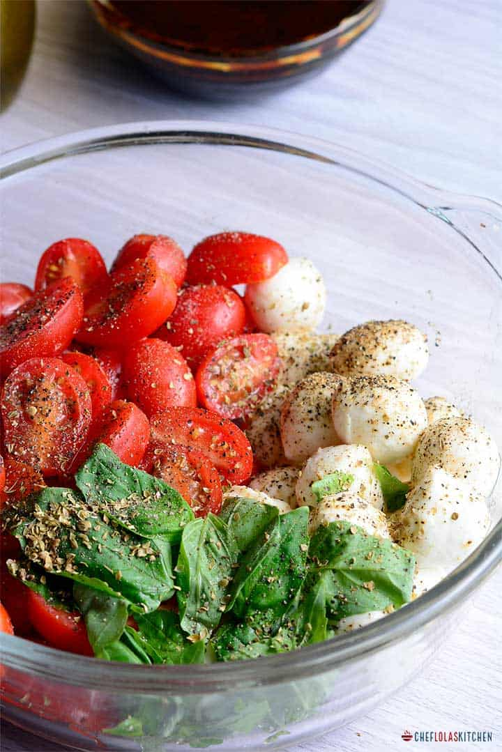 Tomato Mozzarella Salad seasoned with salt, black pepper and oregano in a bowl