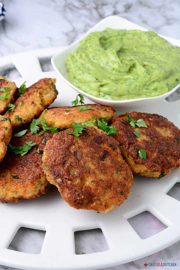 Shrimp cakes served in a large white plate and garnished with parsley.