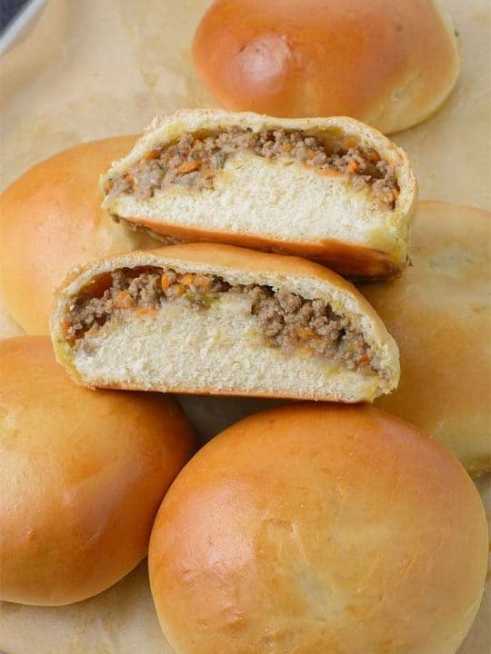 Freshly baked Meat Buns sliced into two to show the delicious meat filling