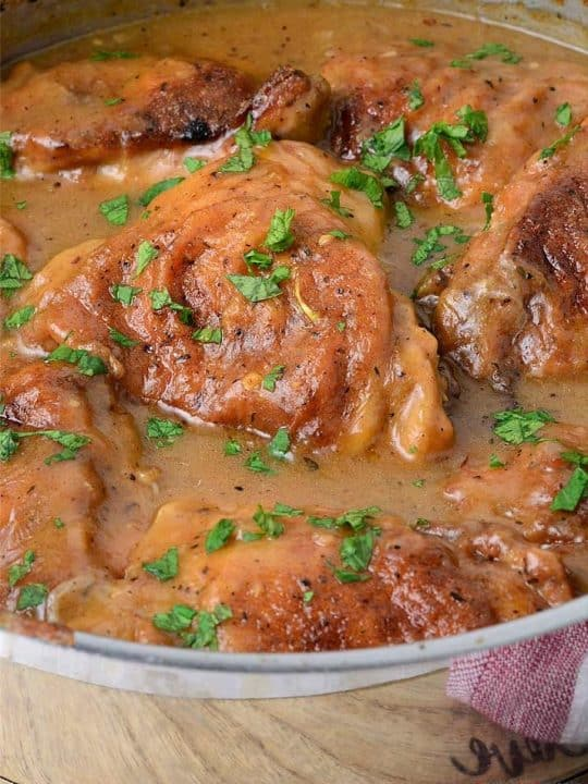 Smothered Chicken filled with gravy in a pan