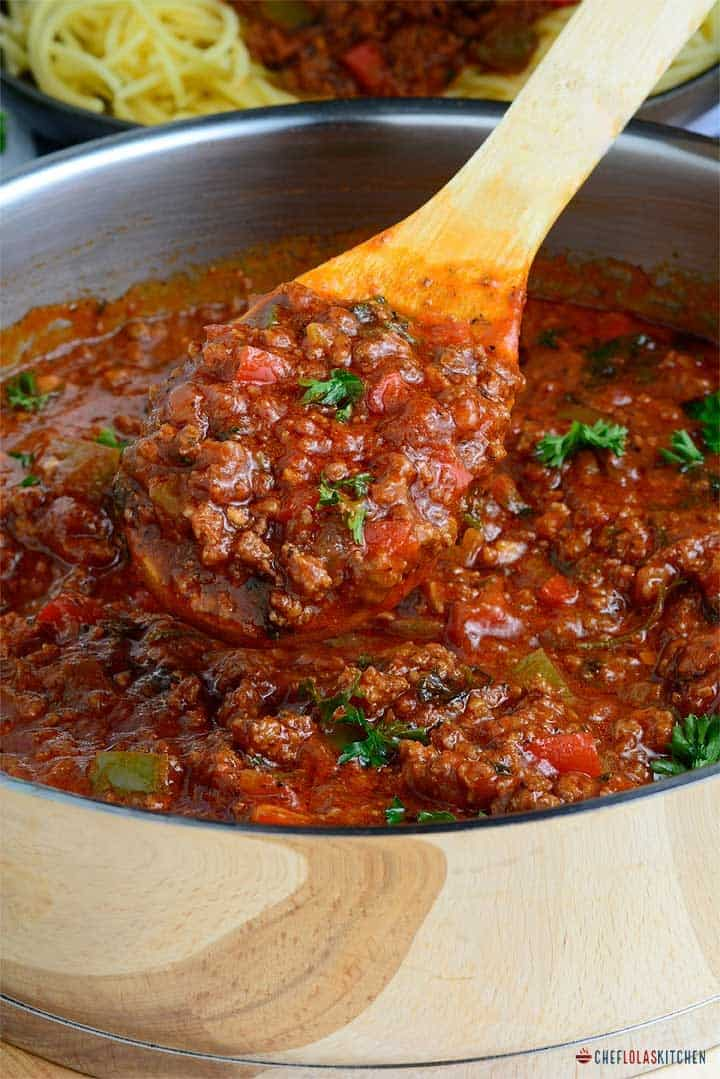 Close look on Pasta sauce scooped with a wooden spoon from a pot