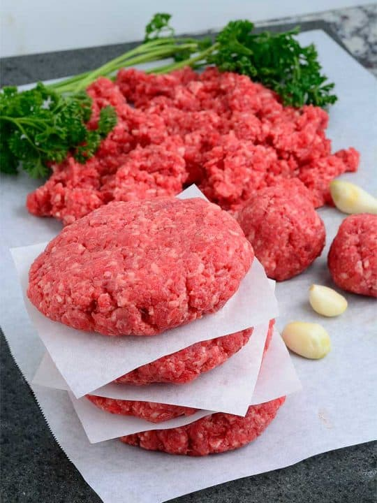 Homemade ground beef in a food processor shaped into patties