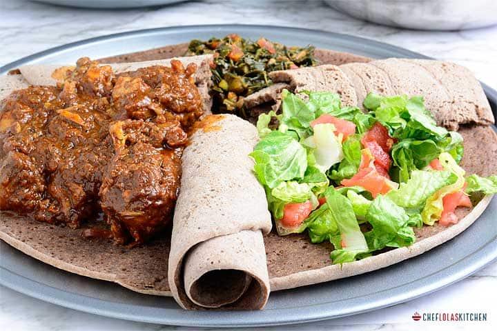 Injera served with doro wat, gomen wat, and salad
